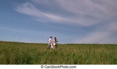 Young couple with bicycles in the green field - Teenage...