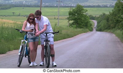 Young couple with bicycles searching route on smartphone in the countryside