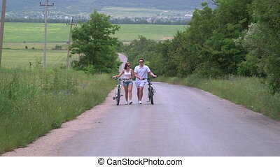 Young couple with bicycles walking along a country road