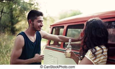 Young couple with bottles on a roadtrip through countryside,...