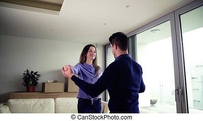 Young couple with cardboard boxes moving in a new home, dancing.