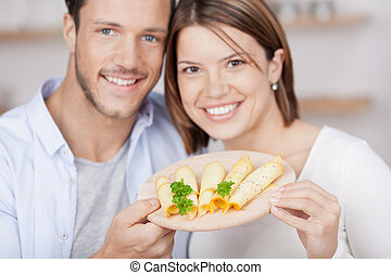 Young couple with cheese platter