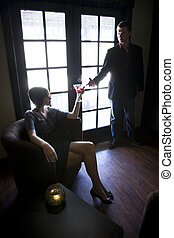 Young couple with cocktails in dark room