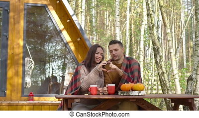 Young couple sitting on the wooden old table in autumn on background of their house