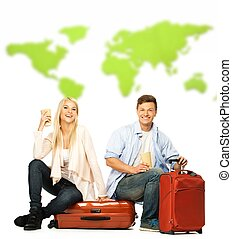 Young couple with coffee cups sitting on suitcases