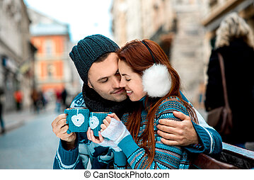 Young couple with coffee in winter outside - Young loving...
