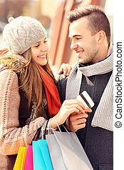 Young couple with credit card shopping in the city