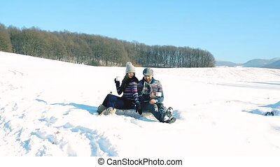Young couple with cup of coffee in winter nature. - Young...