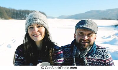 Young couple with cup of coffee in winter nature. - Young ...