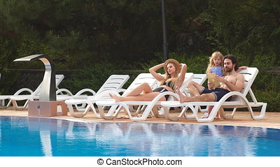 Couple with daughter on Vacation using Digital Tablet near swiming pool