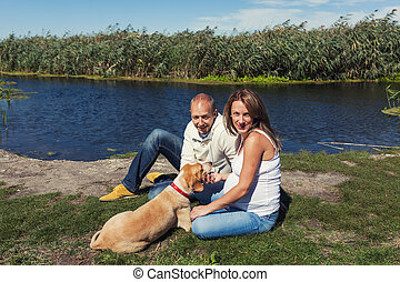 Young couple with dog - Husband and pregnant wife are...