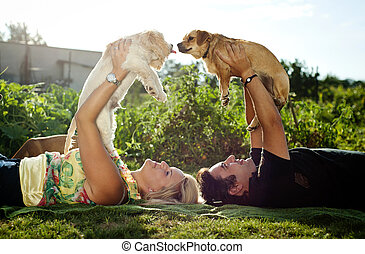 Young couple with dogs - Happy young couple is laying down ...