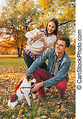 Young couple with dogs pointing on copy space outdoors in autumn