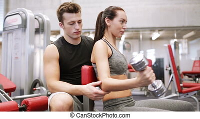 young couple with dumbbell flexing muscles in gym