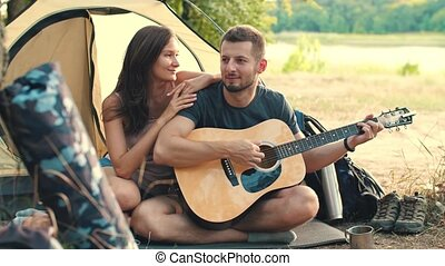 Young couple with guitar in tent singing songs