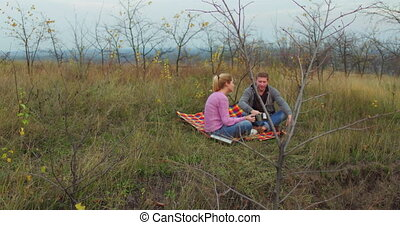 Young couple with hiking circles in his hands sits on litter in nature. Tourists relax and have breakfast on halt. Distant view. High quality 4k footage