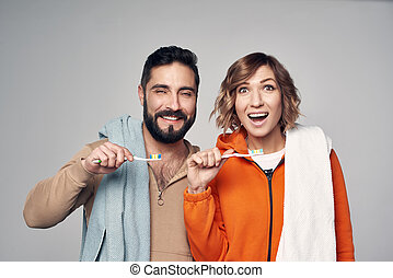 Young couple with home towels and toothbrushes with toothpaste