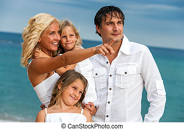 Young couple with kids on beach.