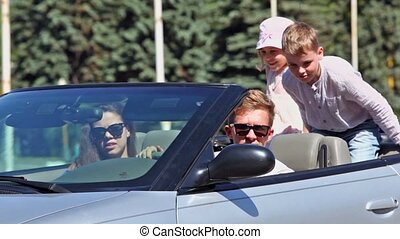 Young couple with kids ride backward in cabriolet at sunny day