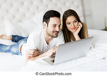 Young couple with laptop in the bed