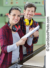young couple with laptop in the carpenter workroom