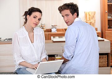 young couple with laptop in the kitchen