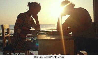Young couple with menu and smartphones in beach cafe during...
