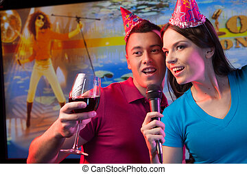 Young couple with microphone standing in bar. Attractive...