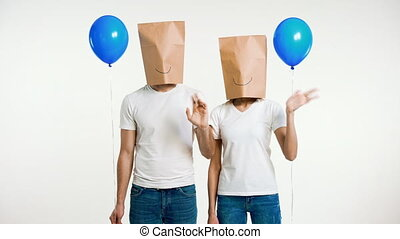 Young couple with paper bag on the head waving hand in ...