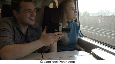 Young couple with retro video camera in train