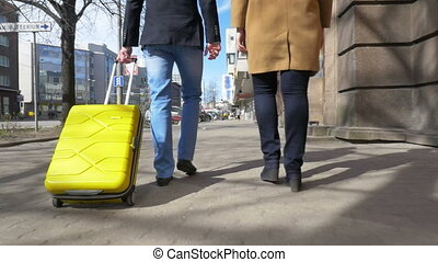 Young couple with rolling bag in the city - Slow motion...