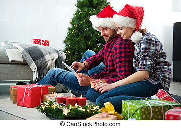 Young couple with Santa Claus hats shopping online Christmas gifts