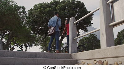 Young couple with skate and bike - Rear view of a mixed race...