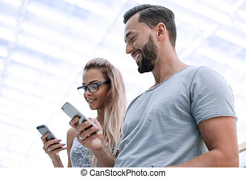 young couple with smartphone on a light background.