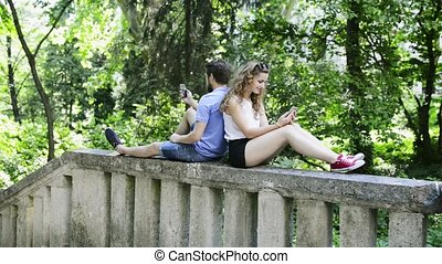Young couple with smartphones in town sitting on concrete...