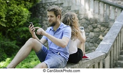 Young couple with smartphones in town sitting on concrete wall.