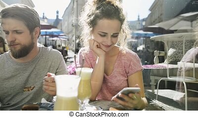 Young couple with smartphones sitting in cafe. - Beautiful...