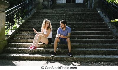 Young couple with smartphones sitting on stairs in town...