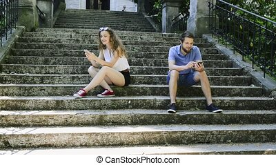 Young couple with smartphones sitting on stairs in town.