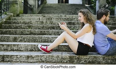 Young couple with smartphones sitting on stairs in town. -...