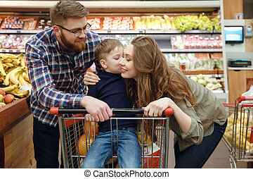 Young couple with son in supermarket