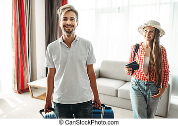 Young couple with suitcases sitting on the couch