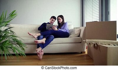 Young couple with tablet moving in a new home, planning how...