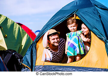 Young couple with their baby daughter in tent, summer