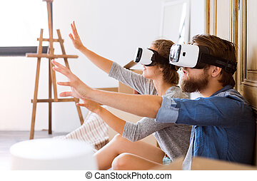 Young couple with VR glasses moving in a new house.