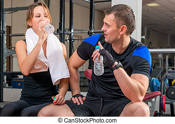 young couple with water after a workout in the gym