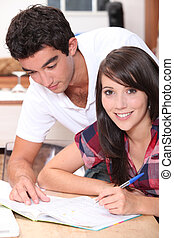 Young couple writing in a book