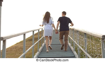 Young coupleclimbs the stairs, rear view - Young couple...