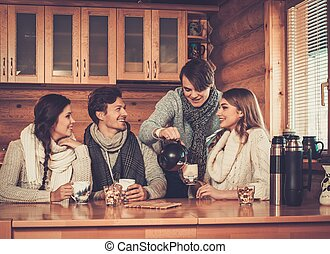 Young couples drinking hot tea in cosy winter cottage ...
