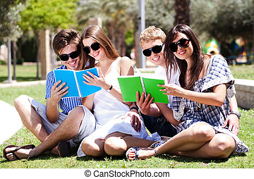 Young couples relaxing in park and reading books
